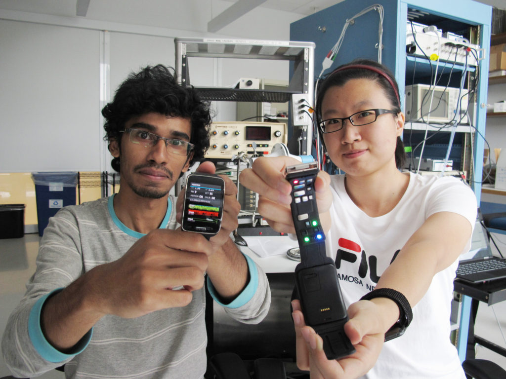 Syed Bashar (left) and Dong Han (right), Ph.D. students in Dr. Ki Chon's lab, are showing Samsung Simband 2.